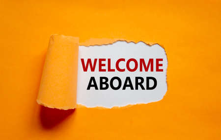 Welcome aboard symbol. Words 'Welcome aboard' appearing behind torn orange paper. Beautiful orange background. Business, welcome aboard concept, copy space.