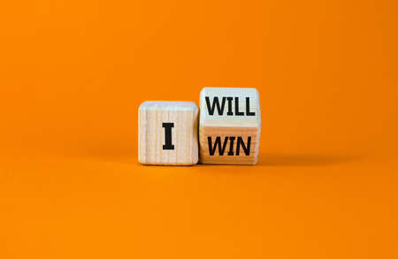 I will win symbol. Turned a wooden cube and changed words i will to i win. Beautiful orange background, copy space. Business, motivational and i will win concept.