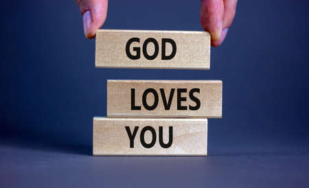 God loves you symbol. Concept words 'God loves you' on wooden blocks on a beautiful gray background, prayer hand. Copy space. Religion and God loves you concept.