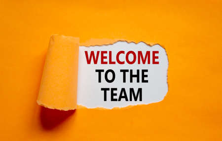 Welcome to the team symbol. Words 'Welcome to the team' appearing behind torn orange paper. Beautiful orange background. Business, welcome to the team concept, copy space.