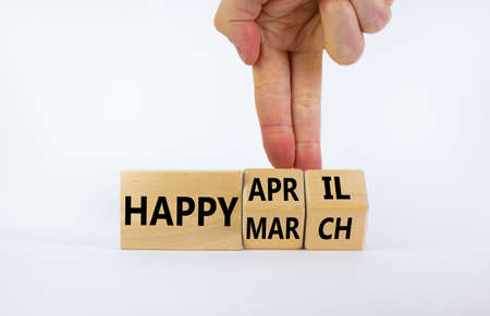Symbol for the change from March to April. Businessman turns wooden cubes and changes words 'Happy March' to 'Happy April'. Beautiful white background, copy space. Happy April concept.