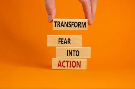 Transform fear into action symbol. Businessman holds wooden blocks with words 'Transform fear into action'. Beautiful orange background, copy space. Business, transform fear into action concept.