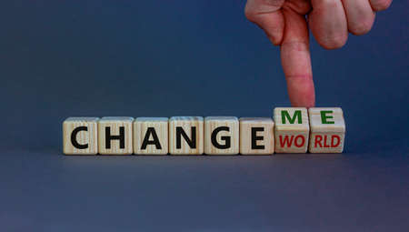 Change world or me symbol. Businessman turns wooden cubes and changes words 'change world' to 'change me'. Beautiful gray background, copy space. Business and change yourself concept.