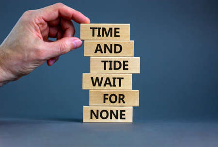 Time to action symbol. Wooden blocks with words time and tide wait for none. Beautiful gray background. Businessman hand. Business and time to action concept. Copy space.