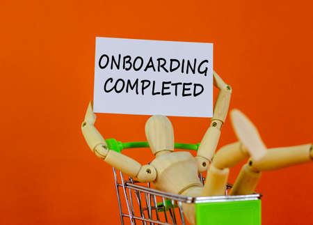 Onboarding completed symbol. White paper. Words 'Onboarding completed'. Wooden model of a human in a shopping cart. Beautiful orange background. Business, onboarding completed concept, copy space.