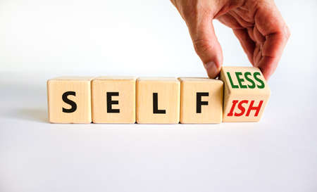 Selfish or selfless symbol. Businessman turns cubes and changes the word 'selfish' to 'selfless'. Beautiful white background, copy space. Business, psuchological and selfish or selfless concept.