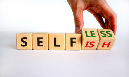 Selfish or selfless symbol. Businessman turns cubes and changes the word 'selfish' to 'selfless'. Beautiful white background, copy space. Business, psuchological and selfish or selfless concept. Banco de Imagens