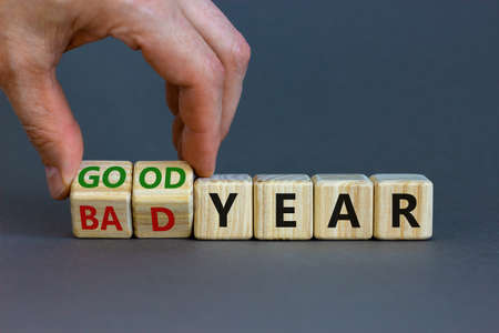Bad or good year concept. Businessman turns cubes and changes words 'bad year' to 'good year'. Beautiful gray background. Business and bad or good year concept. Copy space.