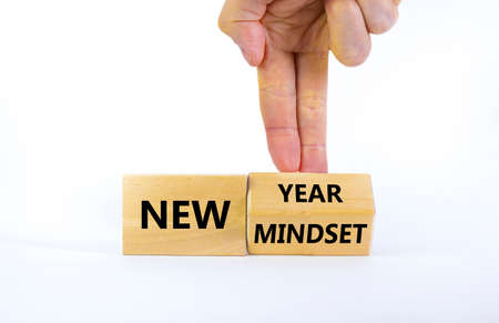 New year and mindset symbol. Businessman turns the wooden block and changes words 'new mindset' to 'new year'. Beautiful white background. Business, new year and mindset concept. Copy space.