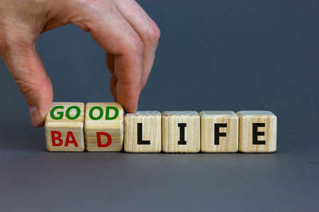 Good life concept for fresh start, new year resolution, dieting and healthy lifestyle. Businessman turns cubes and changes words 'bad life' to 'good life'. Beautiful gray background, copy space.