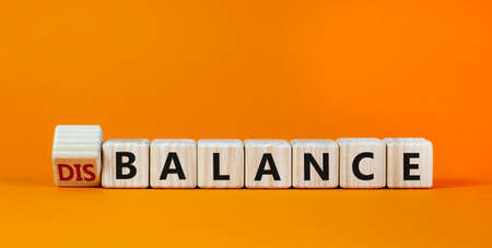 Balance or disbalance symbol. Turned cubes and changed the word disbalance to balance. Beautiful orange background, copy space. Business, balance or disbalance concept.