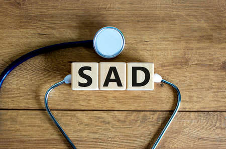 SAD, social anxiety disorder symbol. Concept words 'SAD, social anxiety disorder' on cubes on a beautiful wood background. Medical, psychological and SAD, social anxiety disorder concept. Copy space. Imagens