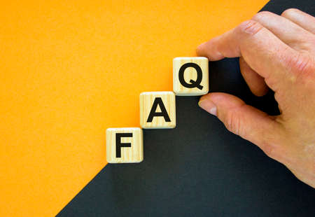 FAQ, frequently asked questions symbol. Concept word 'FAQ, frequently asked questions' on cubes on a beautiful orange background. Businessman hand. Business, FAQ concept. Copy space.