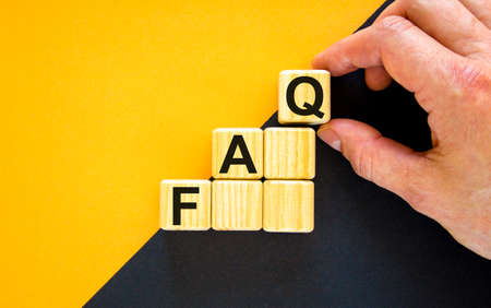 FAQ, frequently asked questions symbol. Concept word 'FAQ, frequently asked questions' on cubes on a beautiful yellow background. Businessman hand. Business, FAQ concept. Copy space.