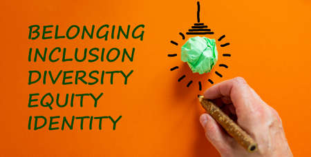 Belonging symbol. Businessman writing 'identity, equity, diversity, inclusion, belonging', orange background. Light bulb icon. Business, belonging, diversity and better inclusion concept. Copy space.
