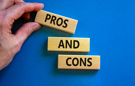 Pros and cons symbol. Wooden blocks with words 'Pros and cons'. Beautiful blue background, businessman hand. Business, pros and cons concept, copy space.