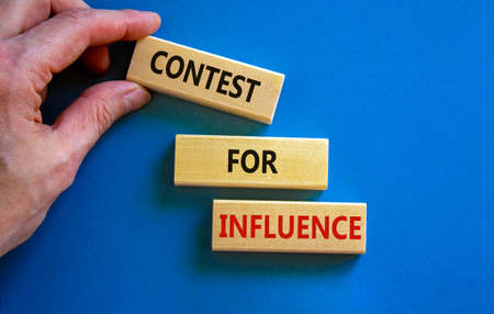 Contest for influence symbol. Wooden blocks with words 'Contest for influence'. Beautiful blue background, businessman hand. Business, contest for influence concept, copy space.