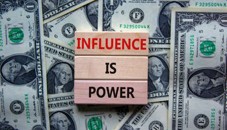 Influence is power symbol. Wooden blocks with words 'Influence is power'. Beautiful background from dollar bills. Business, influence is power concept, copy space.