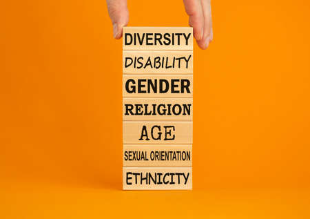 Diversity ethnicity gender age orientation religion disability words written on wooden block. Male hand. Beautiful orange background. Equality and diversity concept. Archivio Fotografico