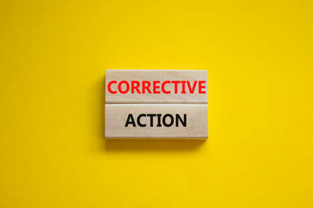 Corrective action symbol. Wooden blocks with words 'Corrective action' on beautiful yellow background. Business and Corrective action concept. Copy space. Stock Photo