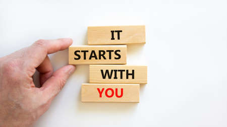 It starts with you symbol. Wooden blocks with words 'it starts with you' on beautiful white background. Businessman hand. Business, motivational and it starts with you concept. Copy space.