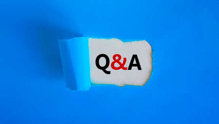 Question and answer symbol. Concept words 'Q and A - question and answer' appearing behind torn blue paper. Beautiful blue background. Business, questions and answers concept. Copy space.