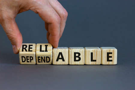 Dependable or reliable symbol. Businessman turns wooden cubes and changes the word dependable to reliable. Beautiful gray background, copy space. Business and dependable or reliable concept.