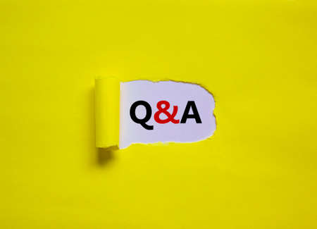 Question and answer symbol. Concept words 'Q and A - question and answer' appearing behind torn yellow paper. Beautiful yellow background. Business, questions and answers concept. Copy space.