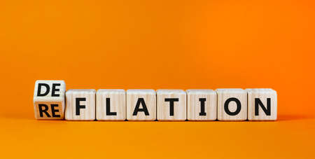 Deflation or reflation symbol. Turned cubes and changed the word deflation to reflation. Beautiful orange background, copy space. Business, deflation or reflation concept. Reklamní fotografie
