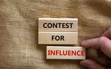 Contest for influence symbol. Wooden blocks with words 'Contest for influence'. Beautiful canvas background, businessman hand. Business, contest for influence concept, copy space. Reklamní fotografie