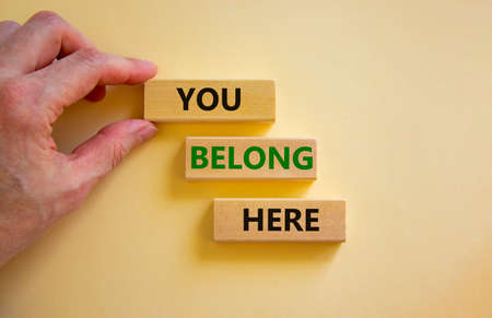 You belong here symbol. Wooden blocks with words 'You belong here' on beautiful white background. Male hand. Diversity, business, inclusion and belonging concept. Standard-Bild