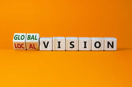 From local to global vision. Turned cubes and changed words 'local vision' to 'global vision'. Beautiful orange background, copy space. Business, local or global vision concept.
