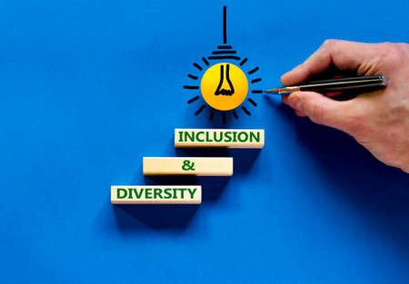 Diversity and inclusion symbol. Wooden blocks with words 'diversity and inclusion' on beautiful blue background. Businessman hand. Light bulb icon. Diversity, business, inclusion, belonging concept.