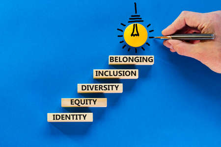 Equity, identity, diversity, inclusion, belonging symbol. Wooden blocks with words identity, equity, diversity, inclusion, belonging on beautiful blue background. Inclusion, belonging concept.