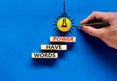 Words have power symbol. Wooden blocks with word 'words have power'. Beautiful blue background. Businessman hand, yellow light bulb icon. Business, words have power concept. Copy space.