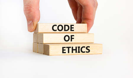 Code of ethics symbol. Concept words 'Code of ethics' on wooden blocks on a beautiful white background. Businessman hand. Business and code of ethics concept. Copy space.