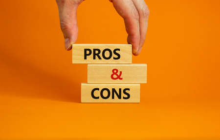 Pros and cons symbol. Wooden blocks with words 'Pros and cons'. Beautiful orange background, businessman hand. Business, pros and cons concept, copy space.