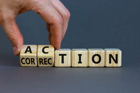 Action or correction symbol. Businessman turns wooden cubes and changes the word correction to action. Beautiful gray background, copy space. Business and action or correction concept.