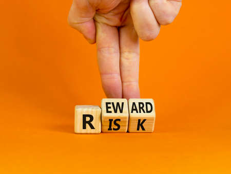 Risk or reward symbol. Businessman turns wooden cubes and changes the word 'risk' to 'reward'. Beautiful orange background. Risk or reward and business concept. Copy space.