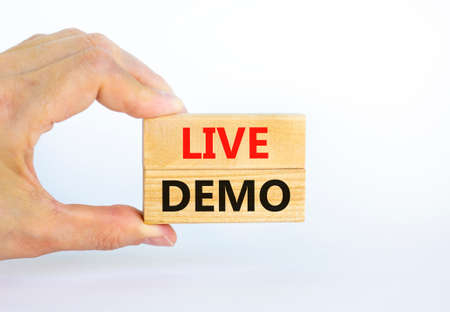 Live demo symbol. Concept words 'live demo' on wooden blocks on a beautiful white background. Businessman hand. Copy space. Business and live demo concept.