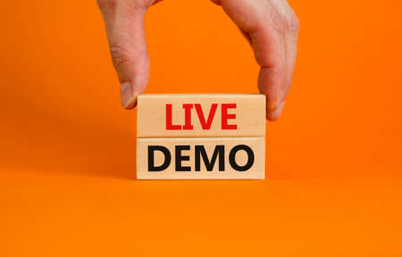 Live demo symbol. Concept words 'live demo' on wooden blocks on a beautiful orange background. Businessman hand. Copy space. Business and live demo concept. Stock Photo