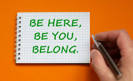 You belong here symbol. Businessman writing words Be here, be you, belong on white note. Beautiful orange background. Business, diversity, inclusion, belonging and you belong here concept. Copy space.
