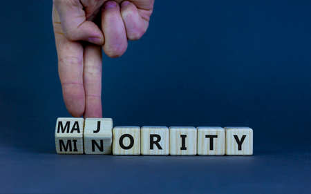 Minority or majority symbol. Businessman turns wooden cubes and changes the word 'minority' to 'majority'. Beautiful gray background. Minority or majority and business concept. Copy space. Reklamní fotografie