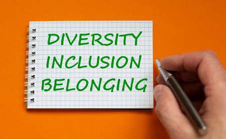 Diversity, inclusion, belonging symbol. Businessman writing words 'Diversity, inclusion, belonging' on white note, orange background. Business, diversity, inclusion, belonging concept. Copy space.
