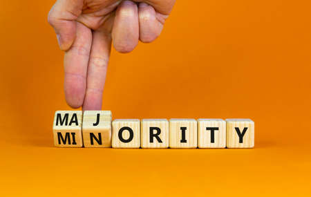 Minority or majority symbol. Businessman turns wooden cubes and changes the word 'minority' to 'majority'. Beautiful orange background. Minority or majority and business concept. Copy space.