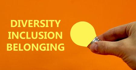 Diversity, inclusion, belonging symbol. Businessman holds yellow shining light bulb. Words 'Diversity, inclusion, belonging', orange background. Diversity, inclusion, belonging concept. Copy space.