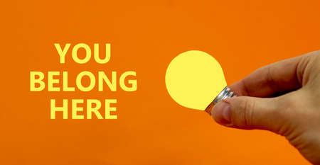 You belong here symbol. Businessman holds yellow shining light bulb. Words You belong here. Beautiful orange background. Diversity, inclusion, belonging and you belong here concept. Copy space.