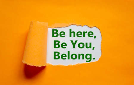 You belong here symbol. Words 'be here, be you, belong' appearing behind torn orange paper. Orange background. Business, diversity, inclusion, belonging and you belong here concept, copy space.
