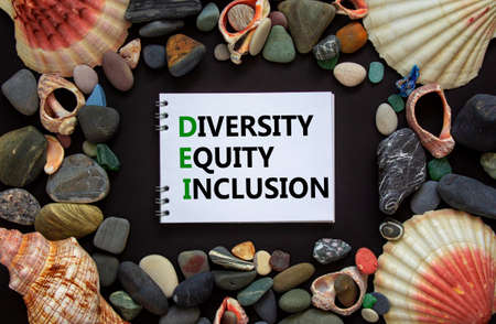 DEI, diversity, equity, inclusion symbol. Words DEI, diversity, equity, inclusion on a beautiful white note, black background. Sea stones and seashells. DEI, diversity, equity, inclusion concept. Standard-Bild