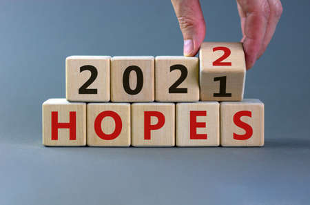 Business concept of planning 2022 hopes symbol. Businesman turns a wooden cube and changes words 'Hopes 2021' to 'Hopes 2022'. Beautiful gray background, copy space. Business and hopes 2022 concept.